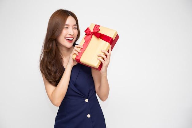 Azjatycki uśmiech kobiety z złote pudełko na białym tle.