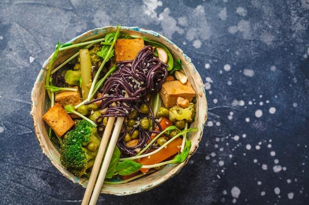 Azjatycki wegan mieszać smażyć z tofu, makaronem ryżowym i warzywami, ciemne tło.