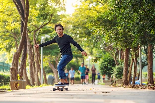 Azjatycki wesoły człowiek gra surfskate lub deskorolka w parku na świeżym powietrzu