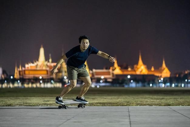 Azjatycki wesoły mężczyzna grający na deskorolce surfingowej lub deskorolce w parku na świeżym powietrzu w nocy