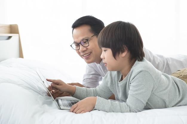 Azjatycki wolny strzelec pracujący w domu i jego syn, student uczący pracę domową online z laptopem.