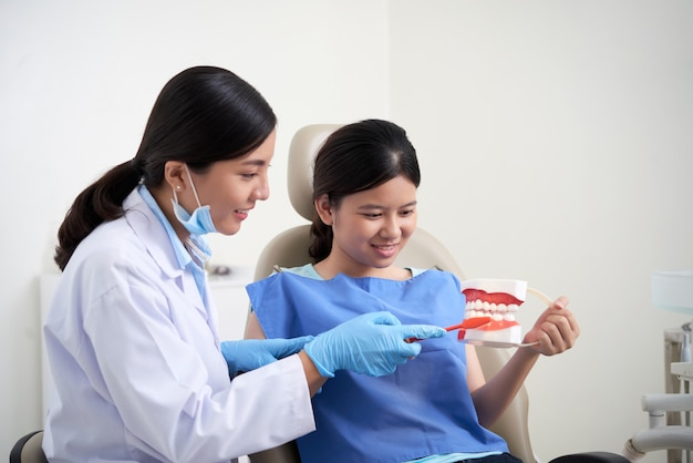 Azjatycki żeński dentysta demonstruje zęby szczotkuje technikę dla pacjenta