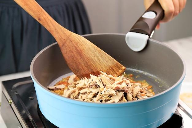 Azjatycki żeński kucharz gotowania pampis tongkol, rozdrobniony tuńczyk z pikantnym smakiem. proces gotowania w kuchni