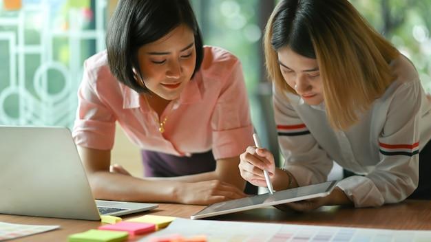 Azjatycki żeński projektant graficzny pracuje wpólnie przy biurem używają laptopu i pastylki.