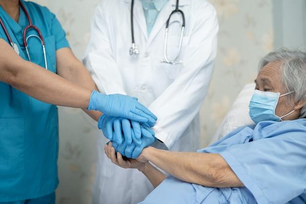 Azjatycki zespół lekarzy i starsza starsza pani pacjentka układają ręce razem jako zespół dla motywacji nowej normy do leczenia infekcji covid-19 coronavirus na oddziale szpitalnym.