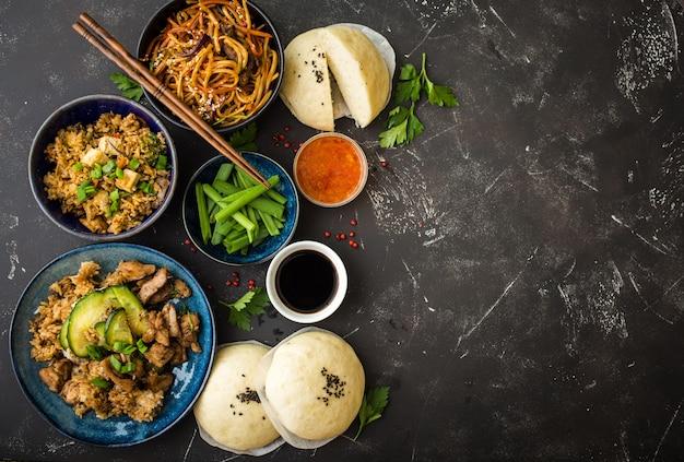 Azjatycki zestaw różnych potraw, ciemne rustykalne kamienne tło. dania chińskie.