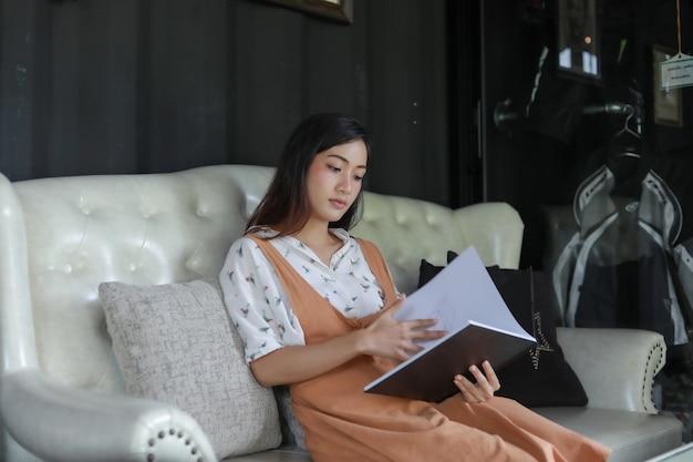 Azjatyckich kobiet czytelnicza książka i uśmiechnięty i szczęśliwy relaksować w sklep z kawą