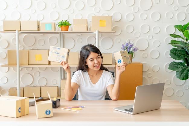 Azjatyckich kobiet właściciel biznesu pracuje w domu z kocowania pudełkiem na miejscu pracy