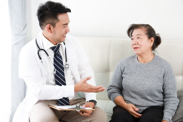 Azjatyckich potomstw doktorski opowiadać z starszą kobietą w szpitalu