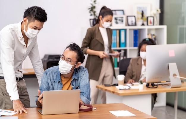 Azjatyckich przedsiębiorców pracujących w biurze na sobie ochronną maskę na twarz