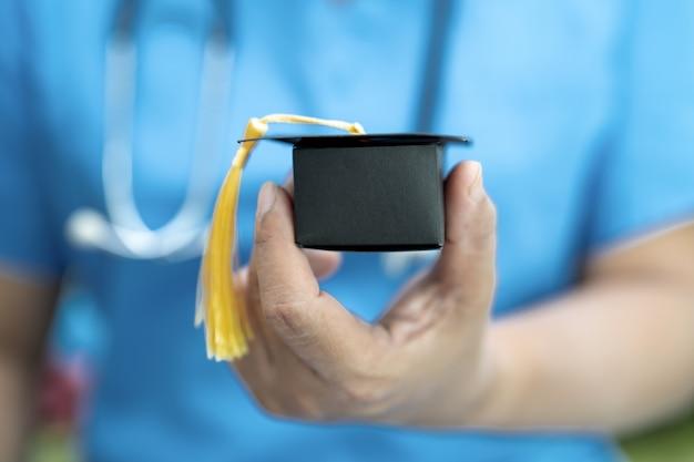 Azjatyckie badania lekarskie uczą się z czapką absolwenta na oddziale szpitalnym