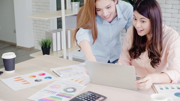 Azjatyckie biznesowe kobiety czuje szczęśliwe ręki podnosili świętować