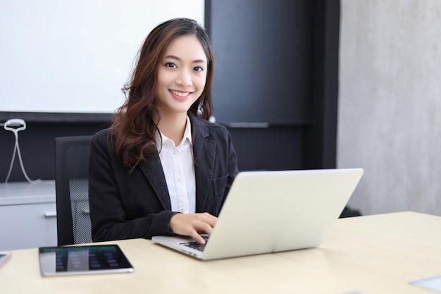 Azjatyckie biznesowe kobiety używa notatnika i ono uśmiecha się szczęśliwych dla pracować