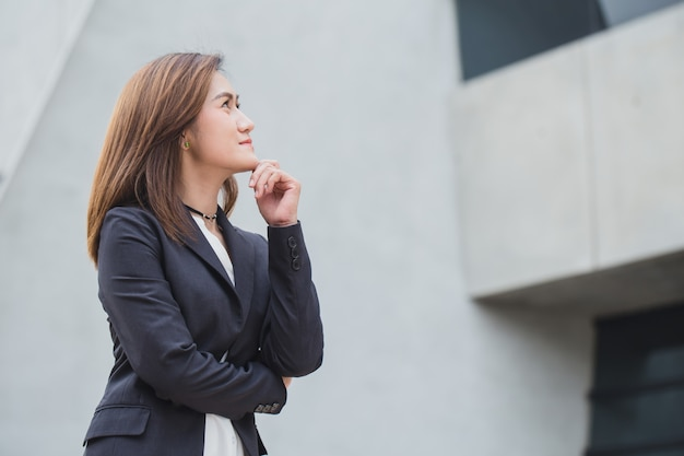 Azjatyckie biznesowe kobiety w główkowaniu z wzroku przyszłościowym przyglądającym przyszłościowym pojęciem
