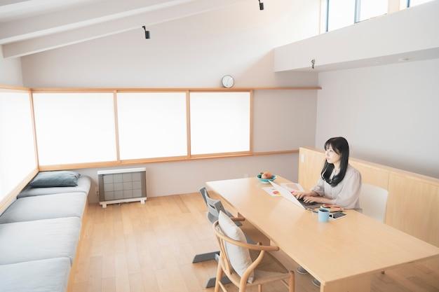 Azjatyckie czarne włosy kobieta pracuje w domu za pomocą laptopa