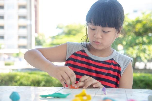 Azjatyckie dzieci bawią się glinianymi kształtami, ucząc się przez zabawę