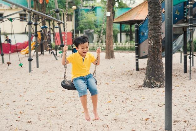 Azjatyckie dzieci huśtają się na placu zabaw