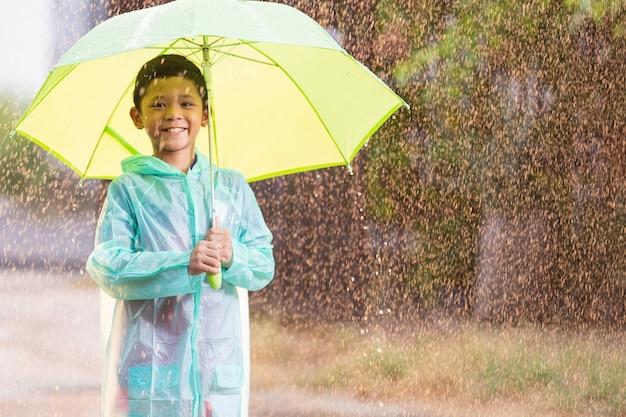 Azjatyckie dzieci rozkładają parasole bawiąc się w deszczu, ona ma na sobie odzież przeciwdeszczową.
