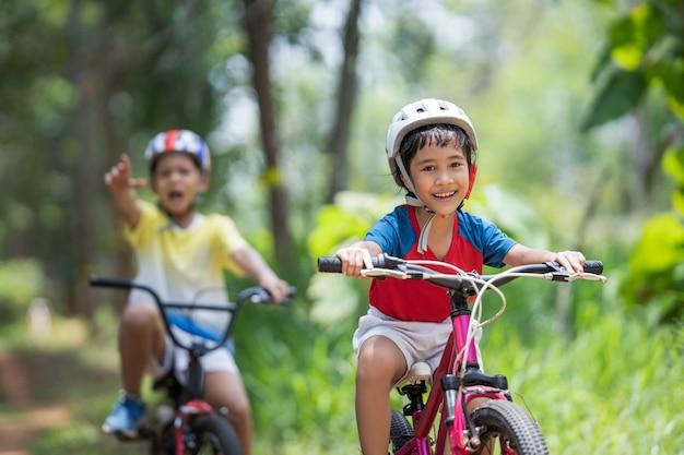 Azjatyckie dzieci są szczęśliwe na rowerze górskim.