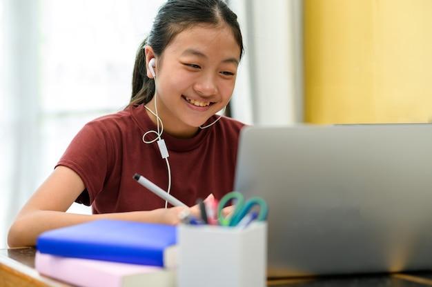 Azjatyckie dzieci samodzielnie uczą się z e-learningiem w domu. koncepcja edukacji online i samokształcenia oraz nauczania w domu.