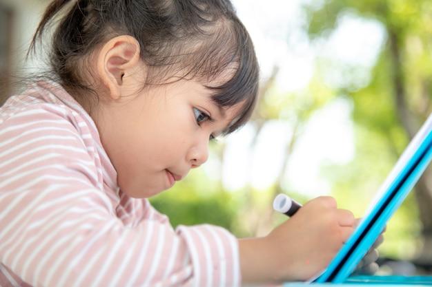 Azjatyckie dzieci uczą się rysować w klasie.
