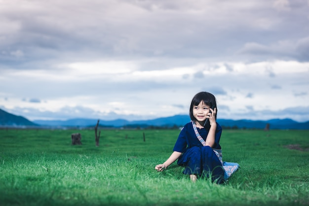 Azjatyckie dzieci w lokalnych strojach używają smartfona, dzwoniąc do mamy, by odebrała ją z pola po zakończeniu połowów