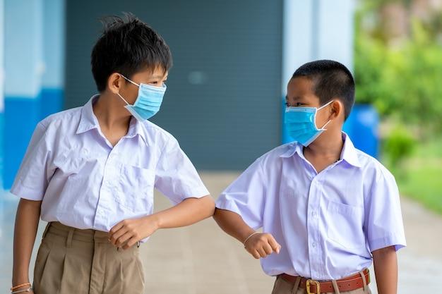 Azjatyckie dzieci w mundurkach szkolnych noszące maskę ochronną w celu ochrony przed covid-19 trzęsą się łokciami, witając się nawzajem, pozdrowienie łokciem, zapobieganie koronawirusowi, dystans społeczny.