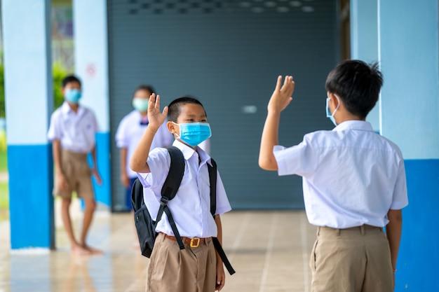 Azjatyckie dzieci w mundurkach szkolnych w masce ochronnej chroniącej przed covid-19 w mundurkach szkolnych w szkole podstawowej pozdrawiają się z dystansem społecznym, nowa normalność.