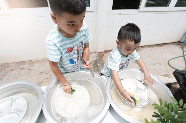 Azjatyckie dzieci, wspólne mycie naczyń i zabawa w domu, uczeń domu i koncepcja edukacji.