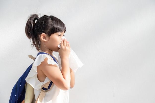 Azjatyckie dziecko dziewczynka chore z kichaniem na nosie i zimnym kaszlem na bibułce, ponieważ słabe lub wirus i bakterie z pogody pyłowej