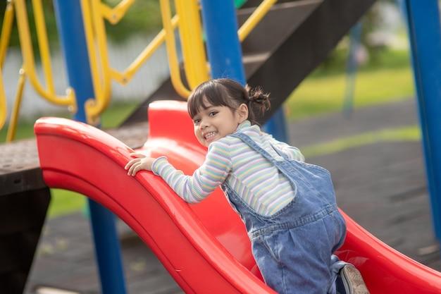Azjatyckie dziecko dziewczynka gra na placu zabaw na świeżym powietrzu. dzieci bawią się na podwórku szkoły lub przedszkola. zdrowa letnia aktywność dla dzieci.