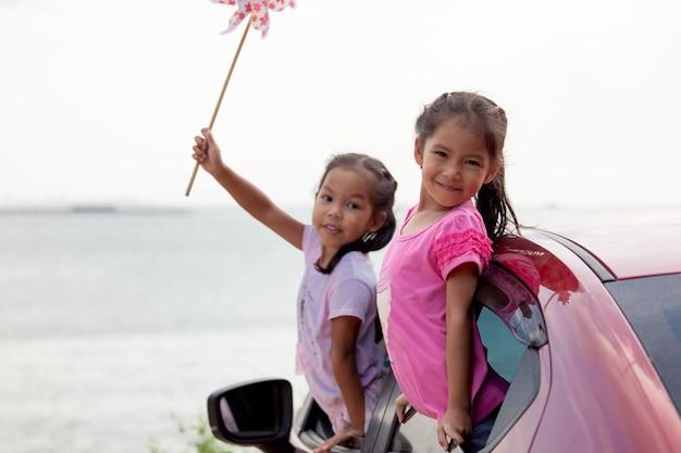 Azjatyckie dziecko dziewczynka gra z turbiny wiatrowej zabawka z siostrą podczas podróży samochodem na plażę