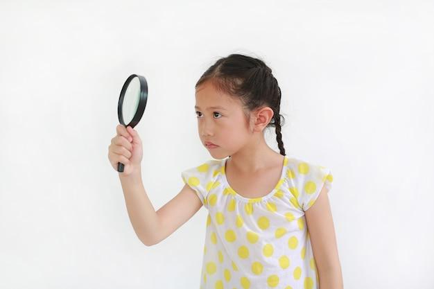 Azjatyckie dziecko dziewczynka patrząc przez szkło powiększające na białym tle