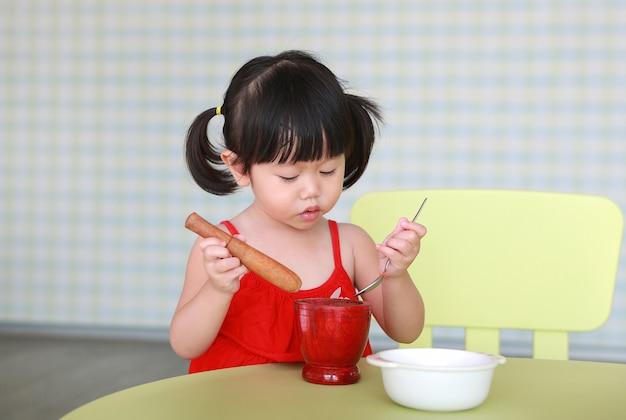 Azjatyckie dziecko gra dziewczyna zrobić zieloną sałatkę z papai lub