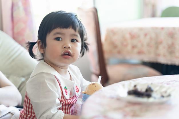 Azjatyckie dziecko jedzenie ciasta czekoladowego w kawiarni