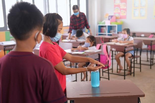 Azjatyckie dziecko używa maski medycznej lub maski chirurgicznej, aby chronić ją przed wirusami, chorobami, zakażeniem covid-19 i koronawirusem. środek do dezynfekcji rąk w zatłoczonym miejscu publicznym.