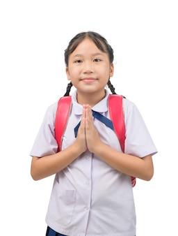 Azjatyckie dziecko w mundurku szkolnym i plecaku z tradycyjnym pozdrowieniem z tajlandii