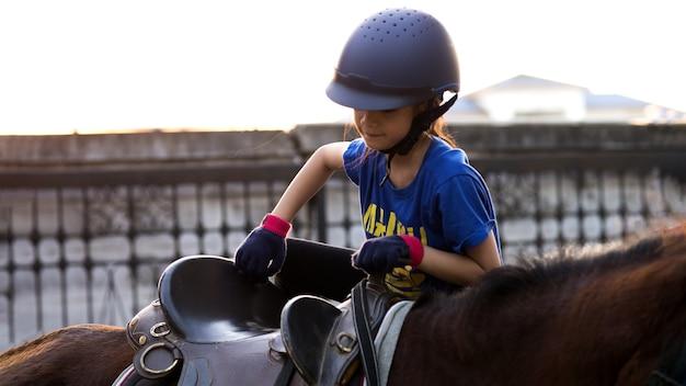 Azjatyckie dziecko w szkole z koniem, jazda konna lub ćwiczenie jazdy konnej na ranczo.