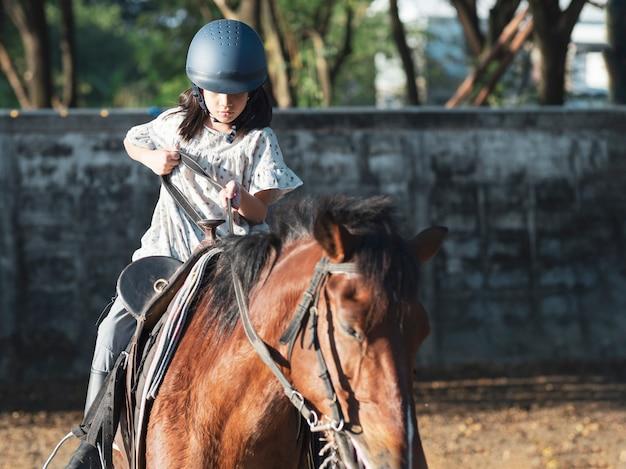 Azjatyckie dziecko w szkole z koniem, jazdą konną lub jazdą konną na ranczo.