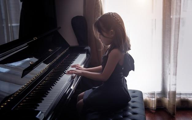 Azjatyckie dziewczynki ćwiczą grę na pianinie, aby ćwiczyć umiejętności muzyczne