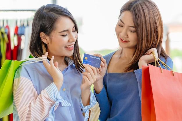 Azjatyckie dziewczyny cieszą się zakupami z bezgotówkowej płatności kartą kredytową z przyjacielem szczęśliwy moment zabawy w sprzedaży sklep razem.