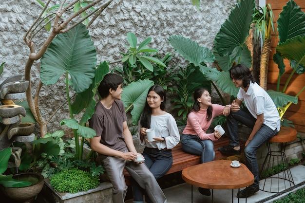Azjatyckie dziewczyny i chłopcy rozmawiają i piją kawę, siedząc na stole i drewnianej ławce w domowym ogrodzie