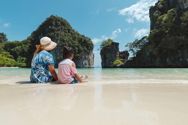 Azjatyckie dziewczyny matka i dziecko siedzi na plaży.