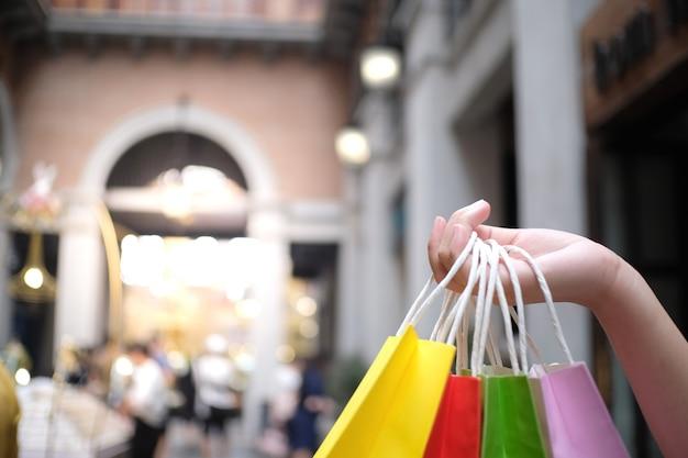 Azjatyckie dziewczyny trzyma sprzedaży torba na zakupy. koncepcja stylu życia konsumpcjonizmu w centrum handlowym.
