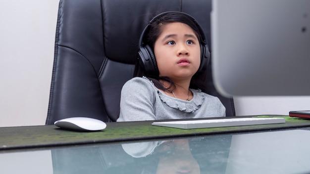 Azjatyckie dziewczyny uczą się online z laptopami. dziecko nosić zestaw słuchawkowy, wpisując klawiaturę notebooka, ucząc się za pomocą lekcji internetowych na kwarantannie. uczniowie uczą się z klasą internetową ze szkoły covid-19