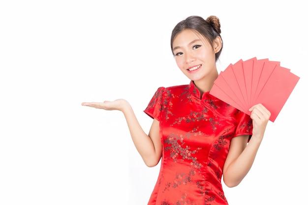 Azjatyckie dziewczyny w tradycyjnych strojach i chińskich kopertach nowego roku.