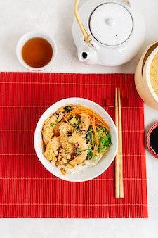 Azjatyckie jedzenie. czajnik i filiżanka, pikantna miska z krewetkami z ryżem, wodorostami i sezamem, awokado na czerwonym bambusowym tle mat z pałeczkami na szarym tle kamienia