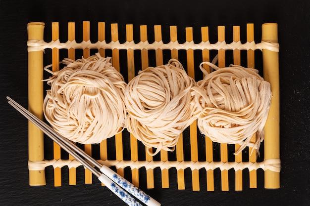Azjatyckie jedzenie domowej roboty orientalny makaron na bambusowej tacy