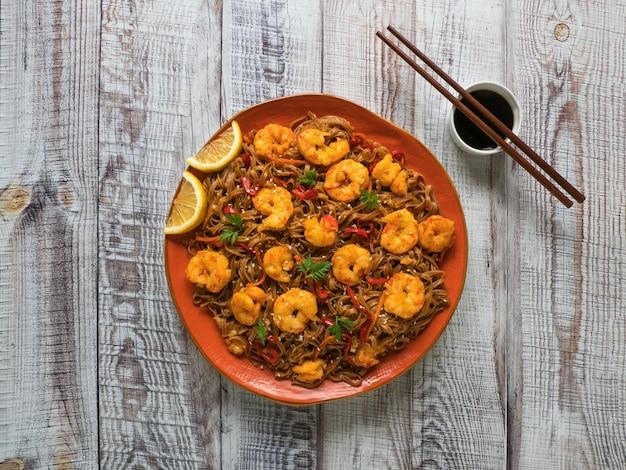 Azjatyckie jedzenie makaron udon ze smażonymi krewetkami, sezamem i pieprzem z bliska na talerzu na drewnianym stole.