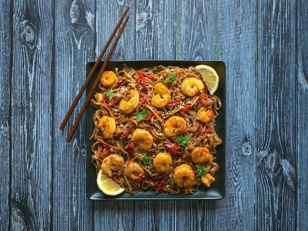 Azjatyckie jedzenie makaron udon ze smażonymi krewetkami, sezamem i pieprzem z bliska na talerzu